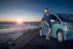 Erstaunliche Schönheitsfrau, die nahe bei ihrem Auto durch das Meer bei dem Sonnenuntergang aufwirft Stockbilder