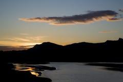Erstaunliche Schattenbildlandschaft der untergehender Sonne reflektierend im Wasser Stockbilder