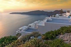 Erstaunliche Sonnenuntergangansicht von der Stadt von Imerovigli zum yown von Oia, Santorini-Insel, Thira, Griechenland Stockfotografie