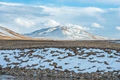 Erstaunliche tibetanische Landschaft mit schneebedeckten Bergen und bewölktem Himmel Lizenzfreies Stockfoto
