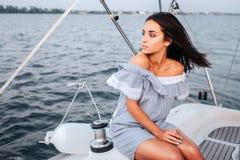 Erstaunliche und schöne junge Frau, die an Bord von Yacht und Blick nach links sitzt Sie ist ruhig und ruhig Frau ist allein stockbilder