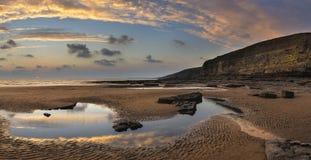 Erstaunliche vibrierende Panoramasonnenunterganglandschaft über Dunraven-Bucht herein Lizenzfreie Stockfotografie