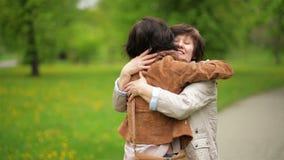 Erstaunlicher Brunette umarmt ihre Mutter mit Liebe und Weichheit im Park Porträt der erwachsenen Tochter und ihrer Mutter stock video