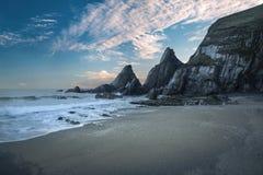 Erstaunlicher bunter Sonnenuntergang über Strandlandschaft mit gezacktem Felsen f Stockbilder
