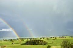 Erstaunlicher doppelter Regenbogen über üppigem Ackerland in den Vorbergen der bayerischen Alpen mit Forggensee und Neuschwanstei Lizenzfreie Stockfotos