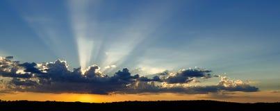 Erstaunlicher drastischer Sonnenuntergang, wenn die Sonnenstrahlen während des clou glänzen Lizenzfreie Stockbilder