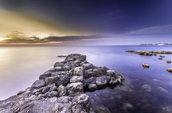 Erstaunlicher erstaunlicher heller Sonnenuntergang und felsiges seacost Stockbild