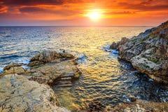 Erstaunlicher felsiger Strand und schöner Sonnenuntergang nahe Rovinj, Istria, Kroatien Stockbild