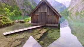 Erstaunlicher Gebirgssee Obersee mit altem hölzernem Häuschen im Frühjahr, Alpen, Deutschland stock video footage