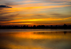 Erstaunlicher goldener Sonnenunterganghimmel mit Reflexion auf ruhigem See Stockbild
