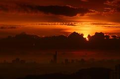 Erstaunlicher Goldsonnenuntergang in der Metropole mit Schattenbildern von Wolkenkratzern Stockbilder