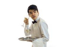 Erstaunlicher junger Kellner in einem Hemd, das ein Glas Wein hält und in Richtung blickt Stockfotografie