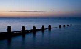 Erstaunlicher langer Berührungssonnenaufgang über ruhigem Meer Stockfoto