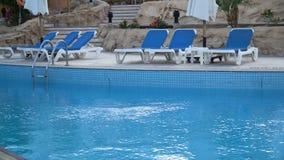 Erstaunlicher leerer Hotelstrand mit fantastischen weißen Daybeds, Ruhesesseln und Sonnenschutz im teuren luxuriösen Erholungsort stock video