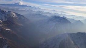 Erstaunlicher Luftbrummenschuß des Schnees umfasste Steinfelsengebirgshügel-Klippenenorme Kettenstrecke auf bewölkter Nebellandsc stock footage
