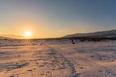 Erstaunlicher orange Sonnenuntergang auf dem schneebedeckten Gebiet mit Abdrücken Russland, Stary Krym Lizenzfreie Stockfotos
