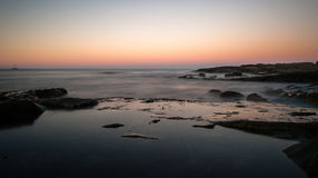 Erstaunlicher Rotglühensonnenuntergang mit ruhigem Ozean Stockbilder