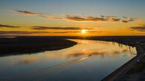 Erstaunlicher Sonnenuntergang über dem Fluss Bunte Reflexion im Wasser stockfotografie