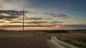 Erstaunlicher Sonnenuntergang über einem Feld mit einer Windmühle im Herbst, timelapse stock footage