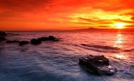 Erstaunlicher Sonnenuntergang über felsigem Meerblick Lizenzfreies Stockfoto
