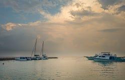 Erstaunlicher Sonnenunterganghimmel und -ansicht über Yachtjachthafen Stockfotos