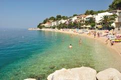 Erstaunlicher Strand mit Leuten, Wohnungen und Palmen in Podgora-Caklje Stockfotografie