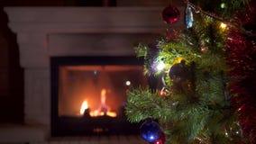 Erstaunlicher Weihnachtsbaum, der bunte Lichtgirlande nahe Kamin mit brennendem Feuerklotz blinkt stock video footage