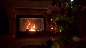 Erstaunlicher Weihnachtsbaum, der bunte Lichtgirlande nahe Kamin mit brennendem Feuerklotz blinkt stock footage