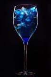 Erstaunliches blaues Cocktail mit Eiswürfeln auf Dunkelheit Lizenzfreie Stockfotos