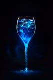 Erstaunliches blaues Cocktail mit Eiswürfeln auf dunklem Hintergrund. Magie L Stockfotografie
