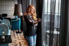 Erstaunliches blondes Schauen durch Fenster Lizenzfreie Stockfotografie