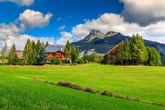 Erstaunliches grünes Feld und alpiner Bauernhof mit Bergen, Altaussee, Österreich Lizenzfreie Stockfotografie