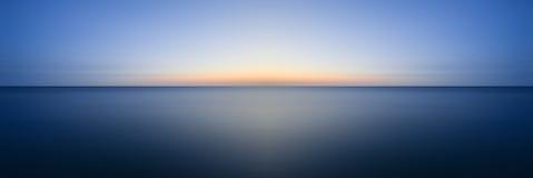 Erstaunliches langes Belichtungsmeerblickbild von ruhigem Ozean bei Sonnenuntergang Stockfotos