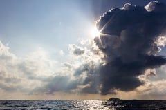 Erstaunliches Licht bricht durch Wolken über dem Meer stockfotos