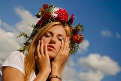 Erstaunliches Mädchen im Blumenkranz träumend auf Blau Lizenzfreies Stockfoto