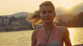 Erstaunliches Mädchen ist, hörend laufend und Musik durch das Wasser Lebenenergie stock footage