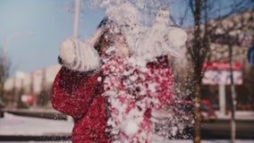 Erstaunliches Nahaufnahmeporträt des netten kleinen Mädchens des Spaßes im warmen Winter kleidet werfenden Schnee in der lächelnd stock video