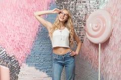 Erstaunliches nettes junges blondes Mädchen mit dem gelockten langen Haar in stilvollem g Stockfotografie