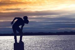 Erstaunliches Schattenbild des Fußballfußballspielerjungen, der Tricks auf dem Strand spielt lizenzfreie stockfotos