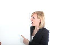 Erstaunte Frau, die auf unbelegten Vorstand zeigt Lizenzfreie Stockfotografie