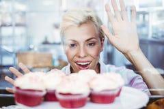 Erstaunte hübsche Frau, die Schalenkuchen betrachtet Lizenzfreies Stockfoto