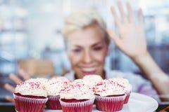 Erstaunte hübsche Frau, die Schalenkuchen betrachtet Lizenzfreie Stockfotos
