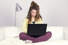 Erstaunte lateinische Frau, die mit ihrem schmutzigen Laptop arbeitet lizenzfreie stockbilder