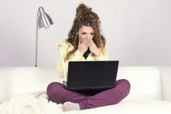 Erstaunte lateinische Frau, die mit ihrem schmutzigen Laptop arbeitet Stockbilder