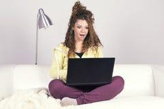 Erstaunte lateinische Frau, die mit ihrem schmutzigen Laptop arbeitet Lizenzfreies Stockfoto