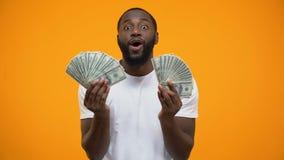 Erstaunter afroer-amerikanisch Mann, der Bündel Dollar, glücklicher Lottogewinner hält stock footage