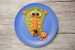 Erstaunter Tiger gemacht vom Salat und von der Karotte auf Platte und Tabelle Stockfoto