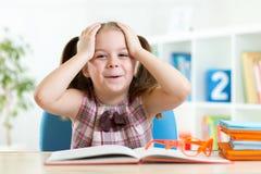 Erstauntes kleines Mädchen liest ein Buch Lizenzfreie Stockfotografie