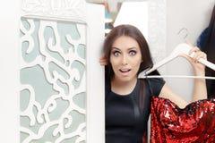 Erstauntes Mädchen, das auf rotem Partykleid in der Umkleidekabine versucht Stockfotos