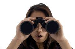 Erstauntes weibliches Überwachen durch binokulares stockfotografie